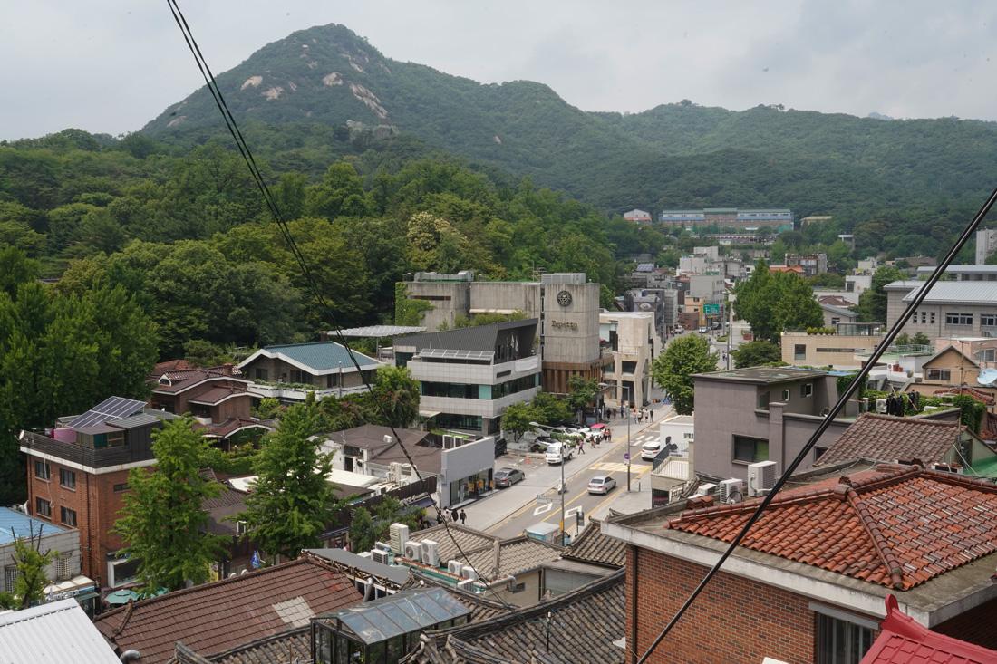 """Même si nous avons déjà entendu le terme (si on s'intéresse un temps soit peu à la culture coréenne), on ne sait pas forcément ce que cela représente. Un peu comme les torii au Japon : on en voit pleins, surtout auFushimi Inari-taisha à Kyoto, pourtant beaucoup ne savent pas ce que c'est concrètement. J'avoue qu'au tout début, étant arrivée totalement novice en Corée du Sud, je croyais que le terme de """"Hanok Village"""" désignait le Namsangol Hanok Village, une reconstruction d'un village hanok dans le parc Namsan. Et je ne me suis pas posée plus de question ... En réalité, le terme """"Hanok"""" désigne les maisons traditionnelles coréennes qui possèdent des caractéristiques bien spécifiques : construites en matériaux naturels, elles se veulent en harmonie avec la nature, ce qui signifie que sont prit en compte l'environnement et les saisons lors de la conception d'une maison hanok. Il existe donc de nombreux types d'hanok différents, puisque le climat est l'un des facteurs les plus importants. Pour plus de détails sur la construction et les caractéristiques des hanok, je vous laisse avec les articles plus détaillés deKoreasowlsetCreative Terre. Du coup, si Hanok désigne des maisons, alors un village d'Hanok n'est rien d'autre qu'un rassemblement de plusieurs maisons traditionnelles coréennes. On peut donc considérer un village Hanok comme un quartier traditionnel."""
